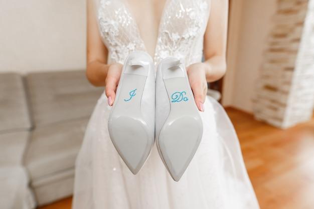 「私は」という碑文とエレガントなブライダルシューズをクローズアップ。梨花の手に白いハイヒールの靴。結婚式の日