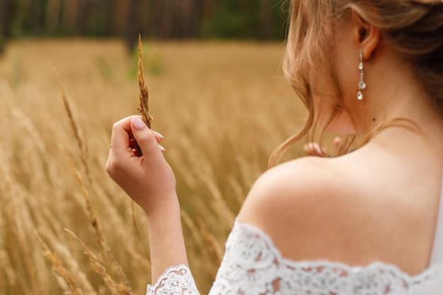 麦畑で屋外の白いドレスの花嫁の優しい肖像画。結婚式の日。美しいネックラインと髪型の側面と裸の肩を持つスタイリッシュな女性。手で小麦の耳を持つ少女