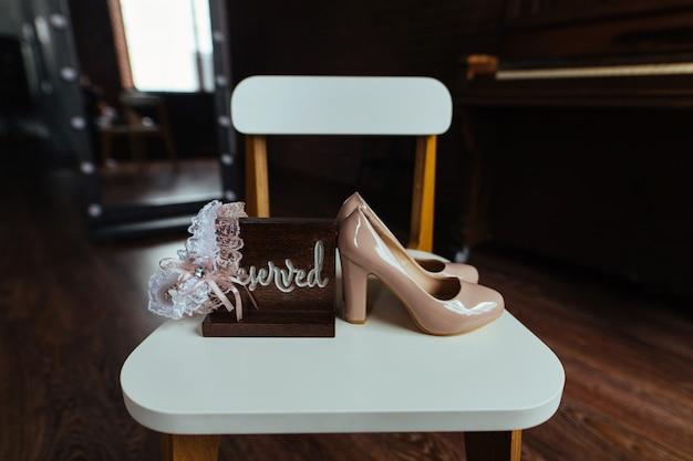 白い椅子にガーターとファッションエレガントな花嫁の靴。屋内のハイヒールと古典的な梨花の靴のペアをクローズアップ。スタイリッシュなインテリアの花嫁のアクセサリー