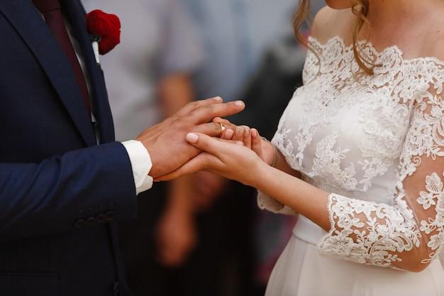 花嫁は、新郎の結婚指輪を着ています。結婚式をクローズアップ。結婚式のカップルは、結婚指輪をクローズアップ交換します。新婚