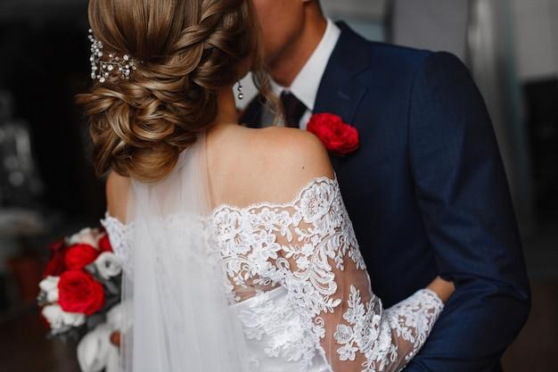 День свадьбы. молодожены целуются на церемонии бракосочетания. страстные объятия влюбленной пары. жених с петлицей нежно обнимает невесту с красным букетом. романтический свадебный момент.
