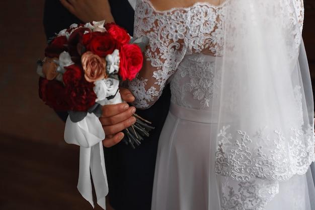 День свадьбы. страстные объятия молодоженов крупным планом. жених с петлицей нежно обнимает невесту с красным букетом. романтический свадебный момент.