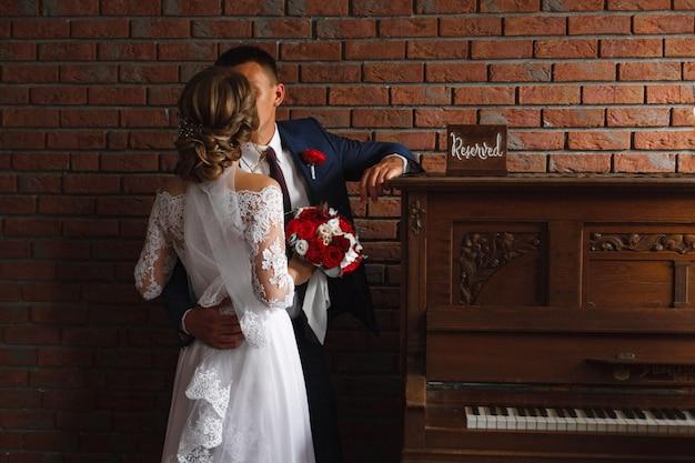 День свадьбы. молодожены обнимаются и целуются в помещении. страстные объятия свадебной влюбленной пары в стильном интерьере.