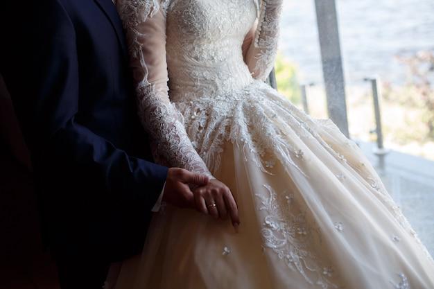 Свадебная пара нежно держит руки крупным планом. мужчина в костюме и женщина в кружевном платье нежно обнимаются. рука об руку. день свадьбы. романтический момент