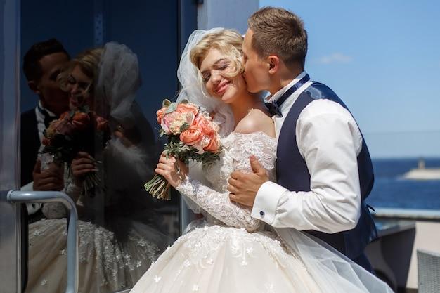 新郎が花嫁に優しくキスする肖像画。結婚式の日。屋外の新婚夫婦の笑顔。結婚式の写真。幸せな結婚式のカップル