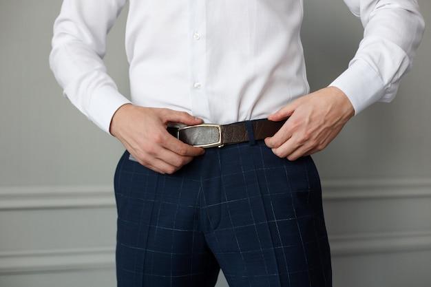 ズボンと白いシャツを着たスタイリッシュな男は、茶色の革ベルトを締めました。男性のフォーマルな服装をクローズアップ。ハンサムな男がスーツを着る