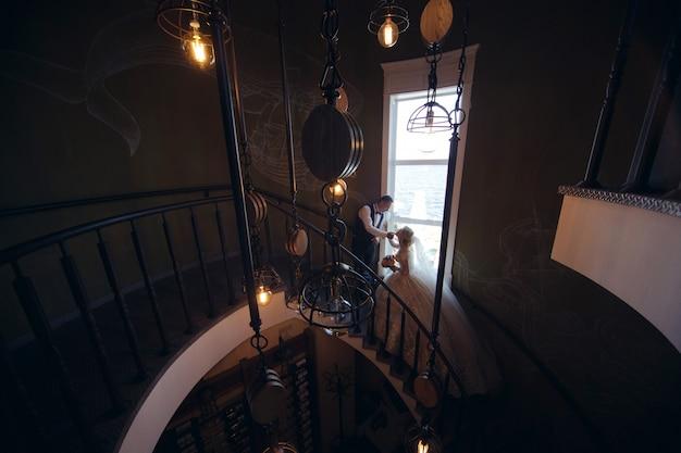 らせん階段にぴったりの新郎新婦。美しいインテリアで愛する新婚夫婦の肖像画。結婚式の日。屋内の愛の結婚式のカップル
