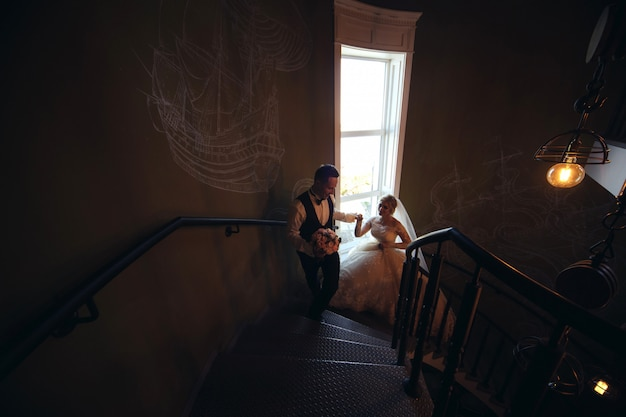 Жених и невеста обниматься на винтовой лестнице. портрет любящих молодоженов в красивом интерьере. день свадьбы. влюбленная пара в помещении