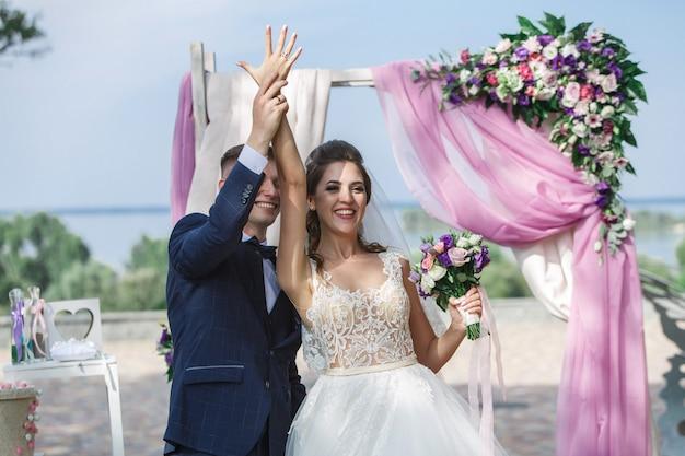 晴れた日の屋外で美しい結婚式。幸せな新郎新婦は結婚指輪を交換します。
