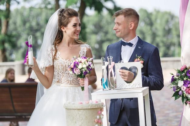 晴れた日の屋外で美しい結婚式。幸せな新郎新婦は結婚指輪と交換します。
