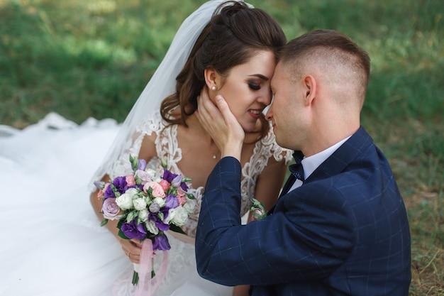 Счастливый жених и невеста после свадебной церемонии в природе. улыбающиеся молодожены обниматься и целовать друг друга на открытом воздухе крупным планом. день свадьбы.
