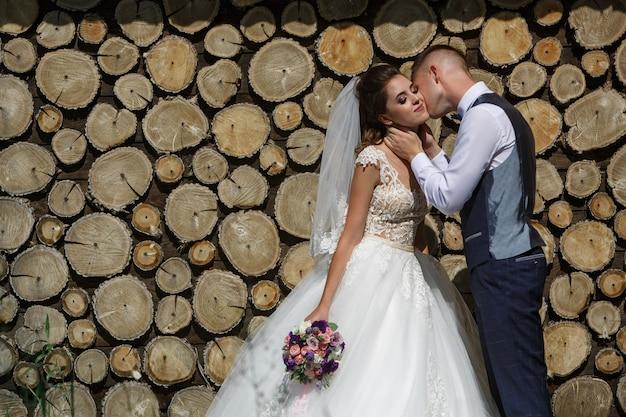 木製の壁に新郎新婦の幸せな笑顔。ロマンチックな瞬間を楽しんでいる若い結婚式のカップル。