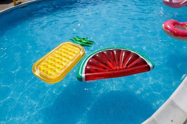 晴れた日に青いプールで膨脹可能なエアマットレス。プールの近くの若者のパーティー。さまざまなマットレスとインフレータブルサークルを備えたプールで泳ぎます。