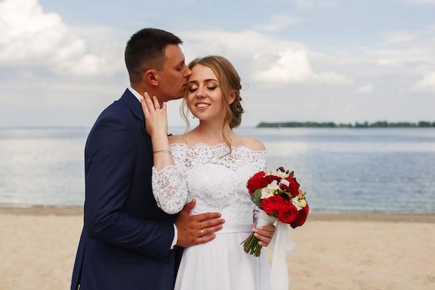 Счастливая невеста и жених, прогуливаясь по реке. романтическая прогулка молодоженов на песчаном пляже в солнечный день. свадебные пары на берегу моря. день свадьбы на открытом воздухе. улыбающаяся невеста и пах, обнимающие и целующие