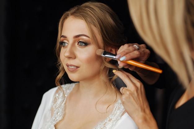 Нанесение кистью для нанесения румян. свадебный макияж. визажист рисует помаду девушки. визажист в процессе. красивая женщина лицо. с вечерним макияжем. рука мастера макияжа