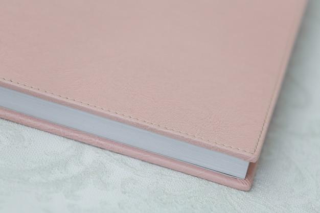 革カバー付きの写真集をクローズアップ。テキストのコピースペースとピンクのフォトアルバム。ハードカバー付きのフォトアルバム。写真の公開用。サンプル写真集。