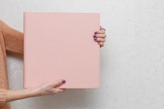 女性は家族の写真集を持っています。人は写真集を見ます。ピンクのフォトアルバムのサンプル。革製のカバー付きの結婚式のフォトアルバム。