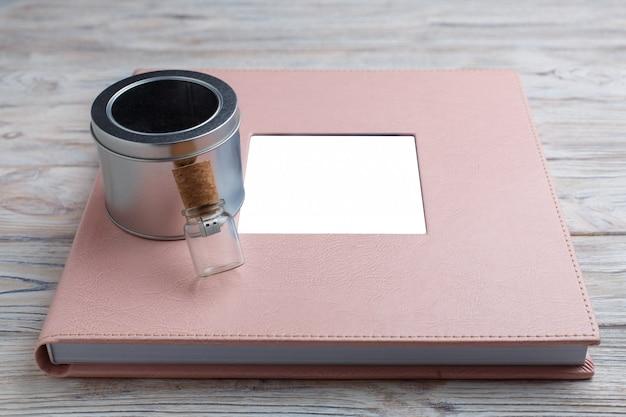 木製のウェディングまたは家族の写真アルバム。フォトブックとボックス付きのフラッシュドライブをクローズアップ。革カバーとシールド付きピンクフォトアルバム。テキストのコピースペースと革の写真集