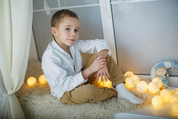 白いシャツとズボンでスタイリッシュな笑みを浮かべて男の子の肖像画。大きな窓の近くのスタジオでポーズをとってハンサムな金髪の少年をクローズアップ。花輪のそばに座ってファッション幸せな少年。