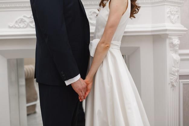 結婚式の新郎新婦。手を取り合って幸せな新婚夫婦をクローズアップ。結婚式の日。美しいちょうど結婚したカップル。ロマンチックなデートに手を繋いでいる愛のカップル。ロマンチックな瞬間をクローズアップ
