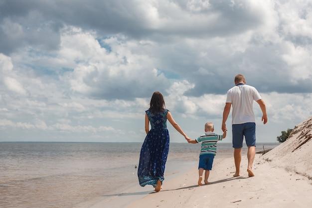 Мама, папа и сын гуляют по песчаному пляжу, держась за руки