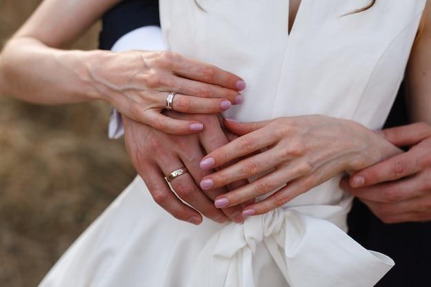 幸せな新婚夫婦が手をつないで優しく抱きしめます。結婚式の日。かわいいばかりの夫婦。ロマンチックなデートに愛の抱擁のカップル。ロマンチックな瞬間をクローズアップ。新郎新婦はお互いを楽しみます