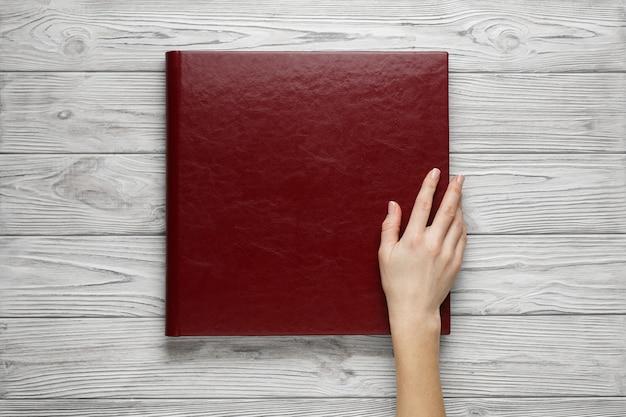革カバー付きの赤い結婚式写真集。スタイリッシュな結婚式のフォトアルバムをクローズアップ。人は正方形の写真集を開きます。テーブルの上の家族のブルゴーニュのフォトアルバム。家族の写真アルバムを持っている梨花の手