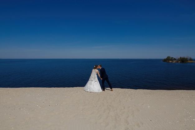 Красивая свадьба пара жених и невеста в день свадьбы на открытом воздухе в голубое небо. жених и невеста в день свадьбы. счастливые молодожены целуются у моря. день свадьбы на морском побережье летом.