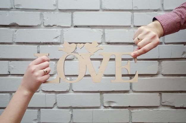 白いレンガの背景に木製の碑文愛をクローズアップ。愛のカップルは、木製の看板「愛」を保持します。結婚式の日。ラブストーリー。新郎新婦の手がテキスト用のスペースと木製の碑文愛を保持します。