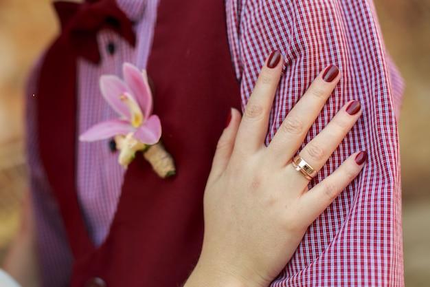 結婚式の日。結婚式で金の指輪を花嫁に優しく抱き締めるボタンホール付きの新郎。結婚式のロマンチックな瞬間。幸せな夫婦。ロマンチックなデートをクローズアップ。ラブストーリー