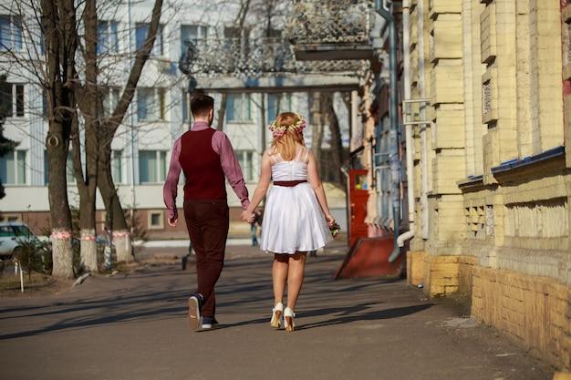 Портрет красивой пары свадьбы в влюбленности напольной. молодожены гуляют по улицам города. день свадьбы. счастливый мужчина и женщина, взявшись за руки и ходить по улице города на романтическое свидание.