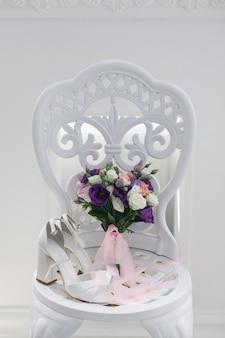 スタイリッシュなインテリアの屋内白い椅子にブライダルシューズ
