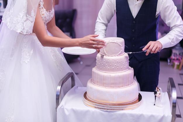 カップルの新郎新婦がレストランでウェディングケーキをカットをクローズアップ。テーブルの上のマスチックで飾られた白いお祝いケーキ