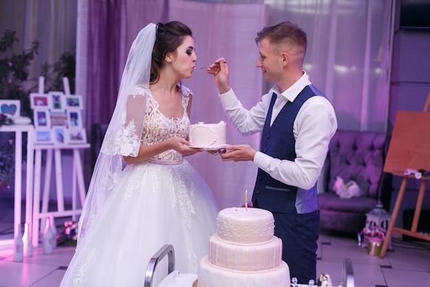 スプーンでパーティーでクリームで美しいウェディングケーキを食べる新郎新婦。結婚式のカップルの新郎新婦は白いお祝いケーキをカットしました。結婚式の日