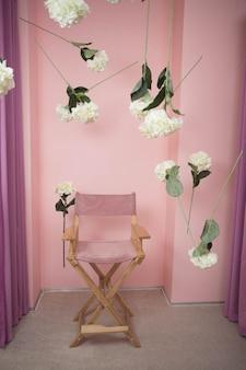 テキストのためのスペースとピンクの背景の木製の椅子。花で飾られた明るいスツール