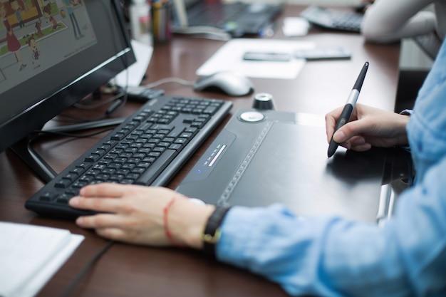 Человек учиться за компьютером крупным планом. женщина графический дизайнер, сидя на компьютере в офисе на рабочем месте крупным планом. женщина дизайнер руки работает на ноутбуке с помощью графического планшета в офисе.