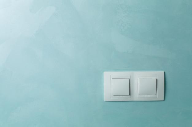 Две белые розетки на стене в помещении крупным планом