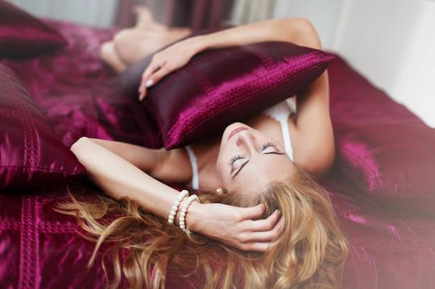ランジェリーのセクシーな女性は赤いシートが付いているベッドにあります。髪型とレースのブラで美しいブロンドの女性は寝室のベッドの上にあるクローズアップ。スタイリッシュなインテリアでベッドに横たわっているロマンチックな裸の女の子