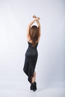 Собрание людей заднего вида. элегантная женщина в моде черное платье и туфли на каблуках сзади вид, портрет в студии. стильная сексуальная брюнетка девушка с привлекательной фигурой, изолированных на белой стене.