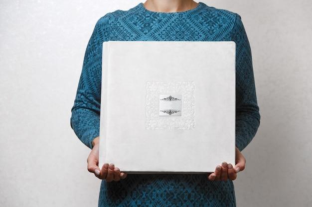 女性が家族の写真集を持っている人は、女性の手で写真集のサンプルベージュフォトアルバムを見て、金属製のシールド付きの布製カバー付きの結婚式の写真集を手にしています。