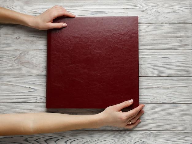 革カバー付きの赤い結婚式の写真集。スタイリッシュな結婚式の写真アルバムをクローズアップ。人が正方形の写真集を開きます。テーブルの上の家族のバーガンディフォトアルバム。家族の写真アルバムを持っている梨花の手