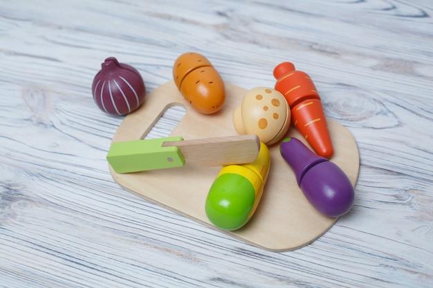 子供のおもちゃの木製野菜。子供たちの成長する木製のゲーム。テキストのためのスペースを持つ木製野菜のセット。子供のプラスチックのおもちゃのキッチン。スライスされたおもちゃの野菜