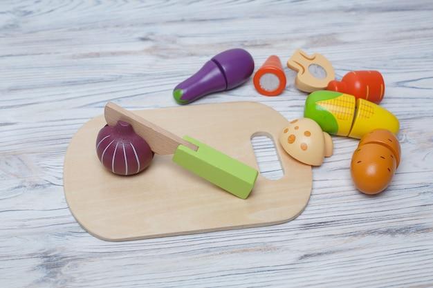 子供のおもちゃの木製野菜。子供たちの成長する木製のゲーム。テキストのコピースペースを持つ木製野菜のセット。子供のプラスチックのおもちゃのキッチン。スライスしたおもちゃの野菜