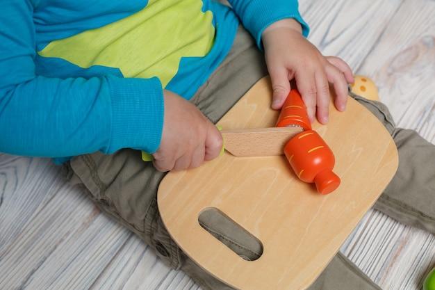少年がシェフで遊んでいるクローズアップ。テキストのコピースペースを持つグッズ木製野菜。面白い開発ゲーム。子供のおもちゃのキッチン。赤ちゃんは木の板にナイフでおもちゃのニンジンをカットします。