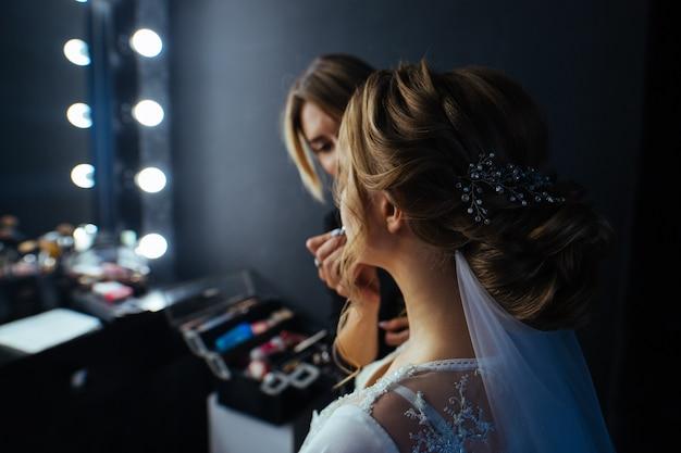 メイクアップアーティストは、ヘアスタイルでモデル化する唇をペイントします。メイクアップアーティストは、ランプが付いている鏡の前で美しい花嫁ブライダルメイクをします。美容コンセプト。仕事でプロのメイクアップアーティストをクローズアップ。
