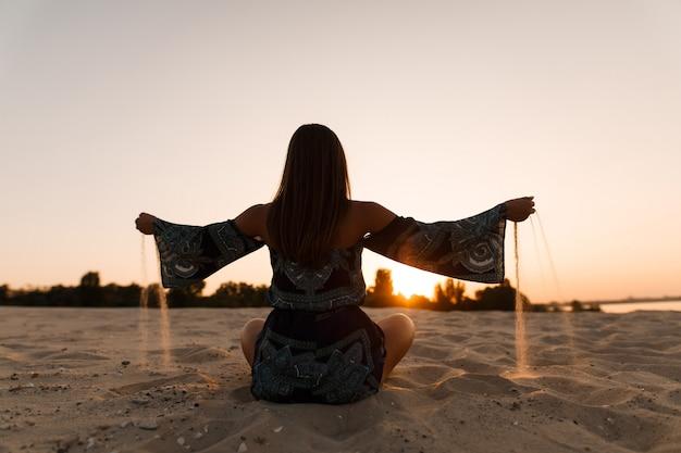 夏の夕日に少女が指を通して砂を注ぐ。手で砂のビーチで砂の上に座っているシルエット女性。孤独な若い女性は、砂浜のビーチで夕日を楽しんでいます