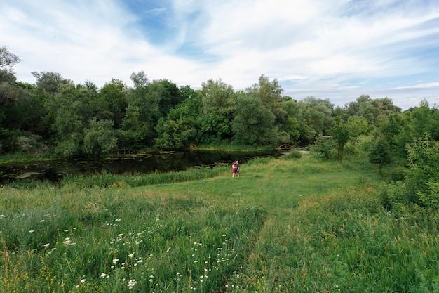 緑の野原に愛情のあるカップル。男と女が歩いて屋外の緑豊かな庭園でハグします。