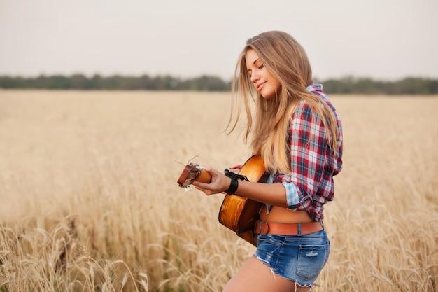 Женщина играет на гитаре в пшеничном поле