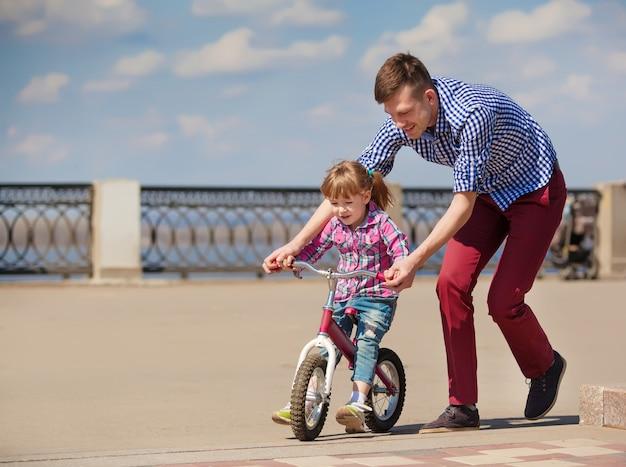 Отец учит дочь кататься на велосипеде