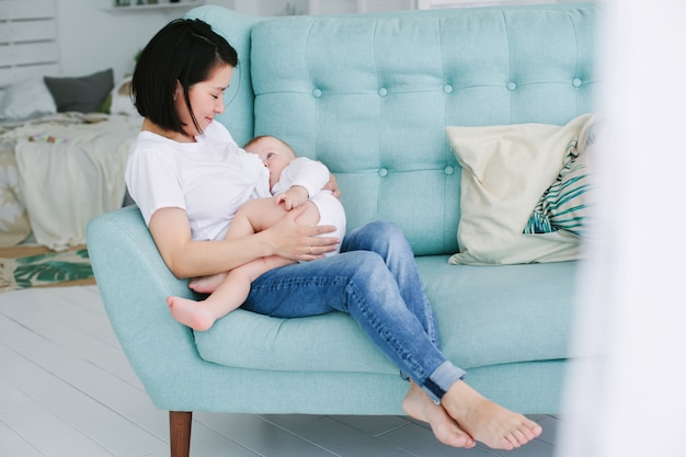 Красивая счастливая молодая азиатская мать прижимаясь ее дочь младенца в спальне